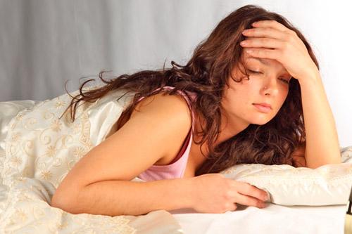 Беременная женщина лежит в кровати