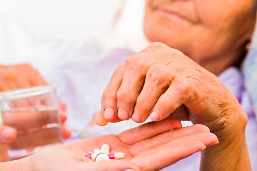 Пожилая женщина принимает лекарства
